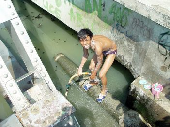 Boy baths in polluted river