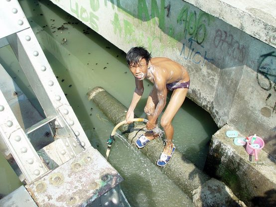 Boy baths in polluted river